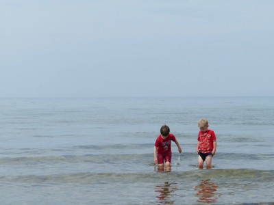 Zion and Matthew wading in the ocean in their clothes