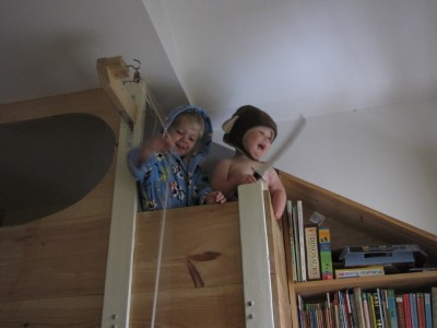 Zion and Lijah looking over the edge of the top bunk, Zion in bathrobe and Lijah in monkey hat