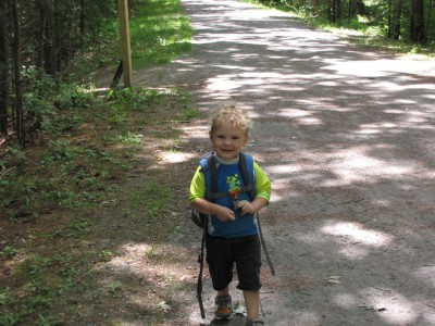 Lijah looking proud wearing Zion's backpack on the trail