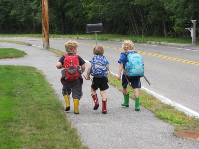 Harvey and two friends walking down the sidewalk in backpacks and rain boots