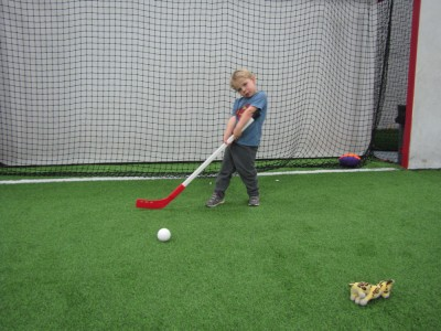 Zion posing with a hockey stick on an indoor turf field