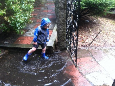 Zion kicking water in a giant puddle
