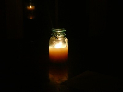 a tallow candle in a jar burning in the dark