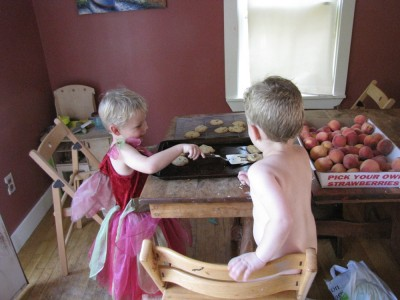 Zion in a dress taking cookies off the sheet, naked Lijah watching