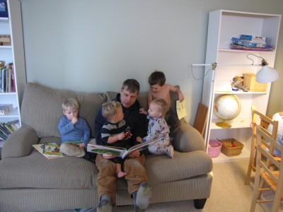 Dan on a couch reading to four little kids