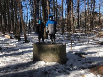 Zion and Elijah standing on the ice in the horse trough in our woods