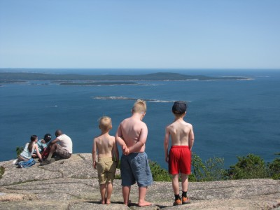 Zion, Harvey, and Nathan shirtless gazing out to sea from a mountaintop