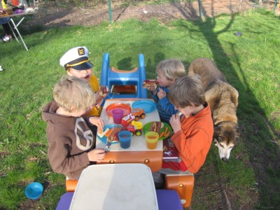boys and friends at the little picnic table eating hot dogs