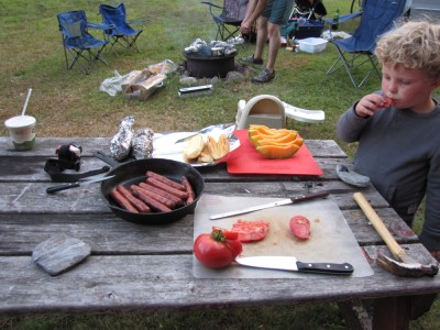 the picnic table with a skillet of hot dogs and a cut-up tomato. and Harvey