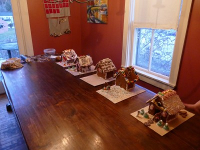 five finished gingerbread houses lined up on the table