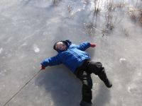 Zion lying on his back on the pond ice, making an ice angel