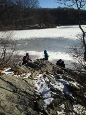 Harvey, Zion, and friends climbing on rocks above an icy pond