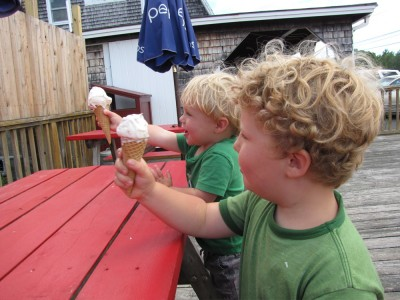 Harvey and Zion sitting at a red picnic table holding ice creams