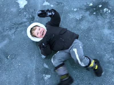 Lijah on his back sliding on the ice