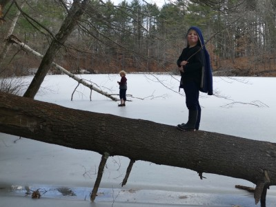 Zion walking on a fallen tree over the ice, Harvey in the background