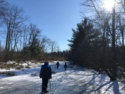 the boys walking through slushy marsh