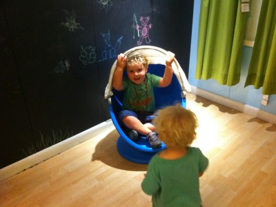 Harvey in a modernist kids chair, Zion waiting his turn