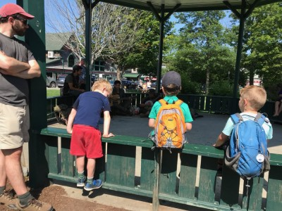 Lijah, Liam, and Henry sitting on the railing of a bandstand watching itinerant musicians