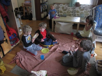 Archibald and Stevens kids eating a picnic on a blanket in the playroom