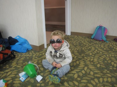 Lijah sitting on a hotel ballroom floor wearing sunglasses upsidedown
