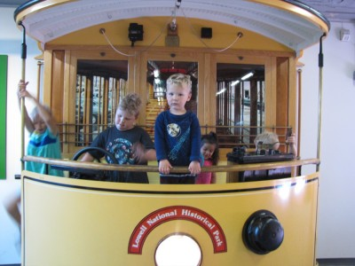 the kids playing on a replica trolley in the museum