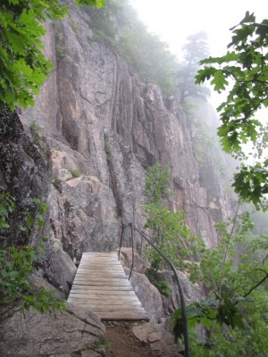 a wooden bridge and cliff face on the Precipice trail