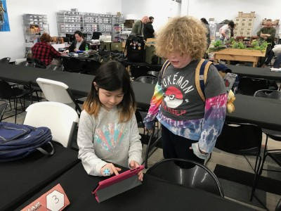 Harvey and a friend looking at an iPad at a Pokemon event
