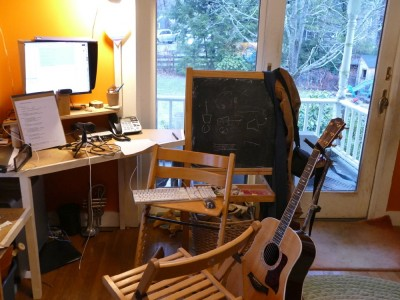 my desk set up with microphone and guitar and propped-up notes