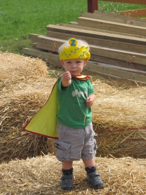 Zion standing on a hay bale wearing a cape and crown