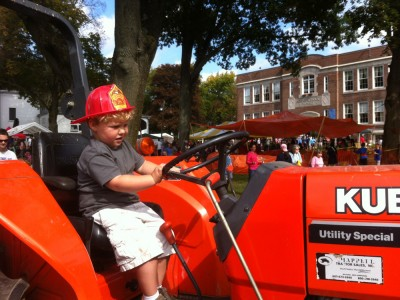 Harvey in the driver seat of a tractor, still wearing the fire hat