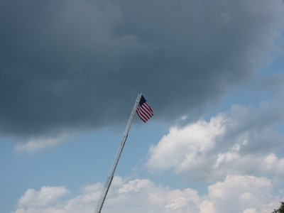 an American flag held high aloft on a fire-engine's ladder