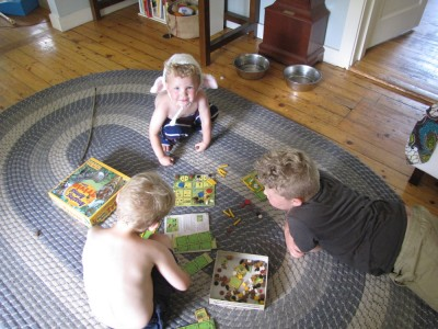 Harvey and Zion playing a board game on the rug, Lijah watching