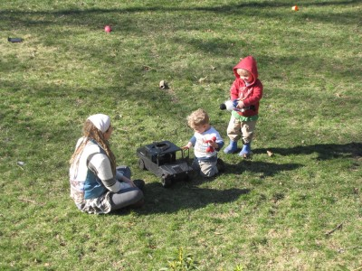 Mama, Lijah, and Zion playing with vehicles and stuffed animals on the green lawn