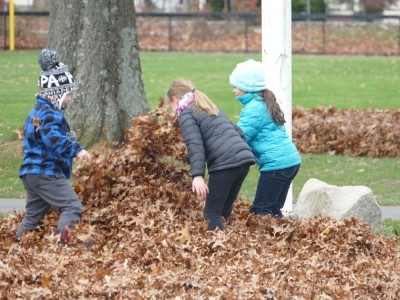 Zion and friends burying someone in leaves