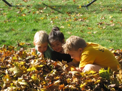 Harvey, Zion, and Kamilah playing in the leaf pile