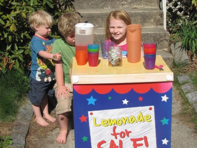 Harvey and Zion (both looking grumpy) with a friend and their lemonade stand