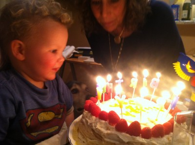 Lijah looking at a birthday cake glowing with the light of candles spelling out