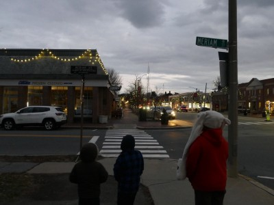 the boys walking towards the Christmas-lighted Lexington commercial stretch
