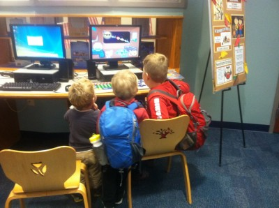three boys captivated by a computer game at the Billerica library
