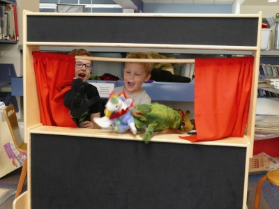 Lijah and Jack doing a puppet show at the library