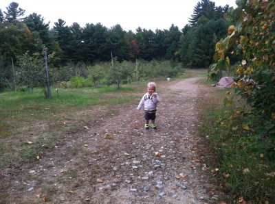 Lijah walking back through the orchard, munching on an apple