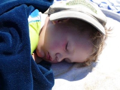 Lijah sleeping on the beach with my cap over his face