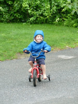 Lijah riding a bike with training wheels