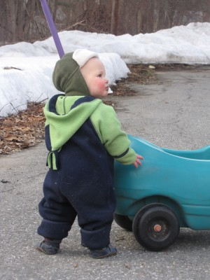 Lijah in his snowsuit walking in the road holding on to a push car