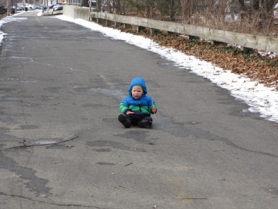 Lijah sitting down in the middle of the bike path