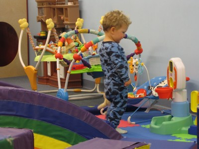 Lijah playing among many toys in a playspace