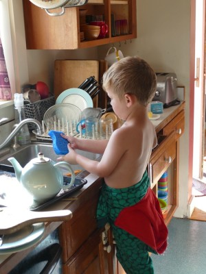 Lijah washing the dishes in his PJs