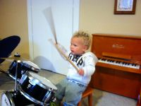 Lijah wailing on the mini drum kit in front of the mini piano