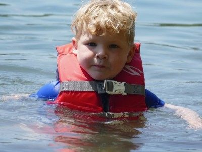 Lijah in his red life jacket almost chin deep in water