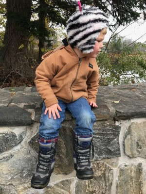 Lijah in cold-weather gear sitting up on a wall